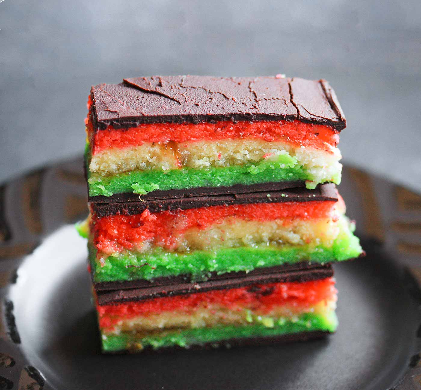 Three Italian Rainbow Cookies stacked on a plate.
