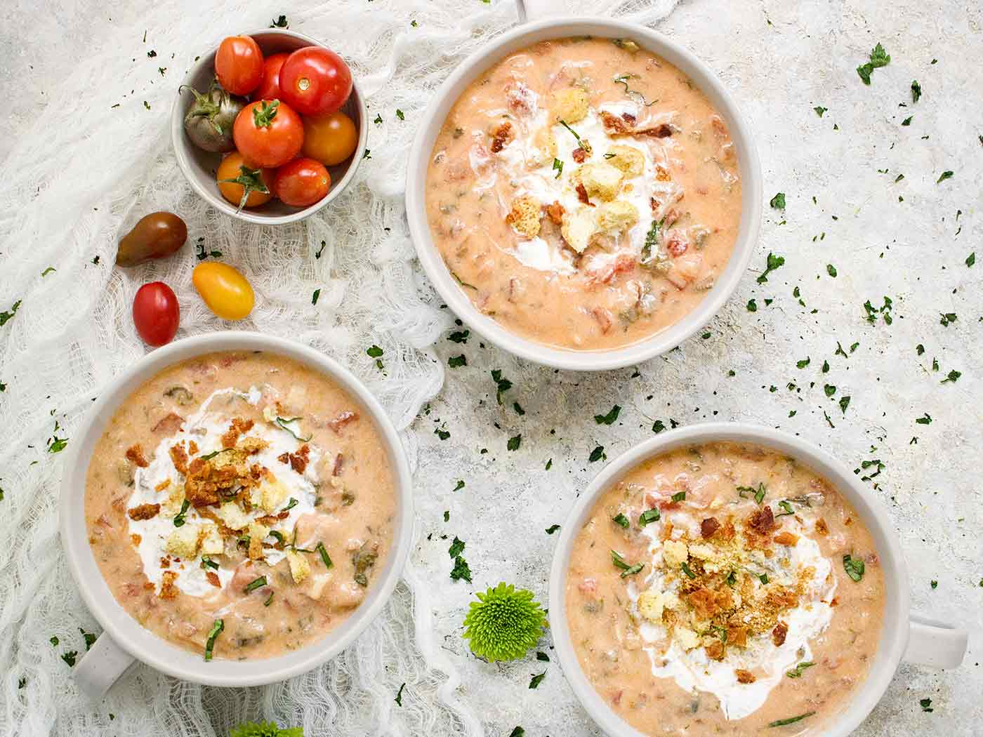 Three mugs of BLT Soup, swirled with creme fraiche and topped with crushed croutons