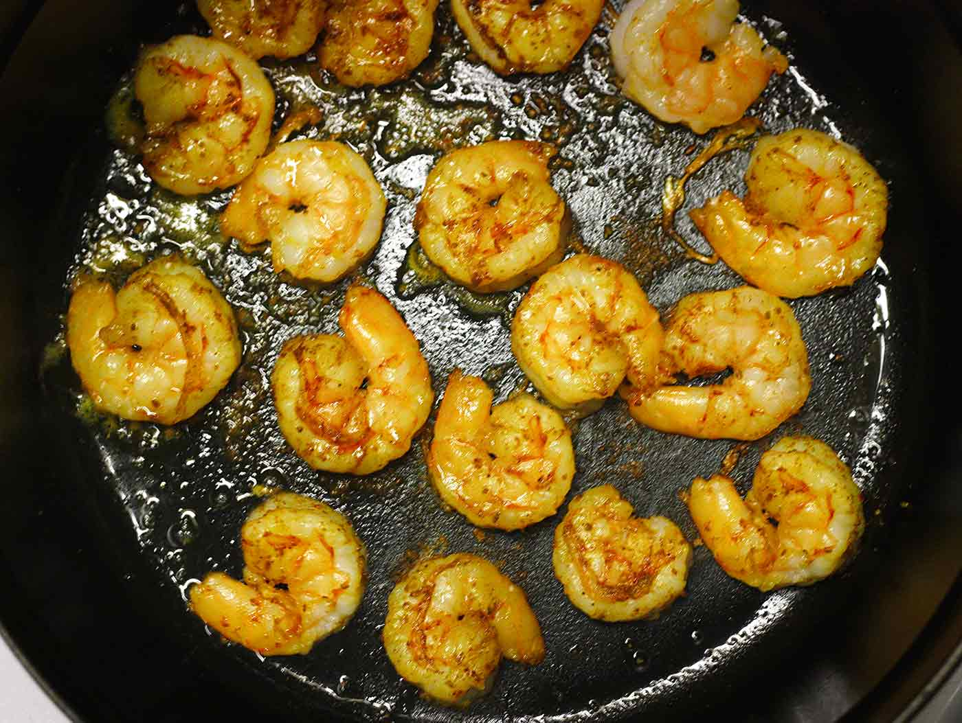 Curried shrimp cooking in a cast iron skillet