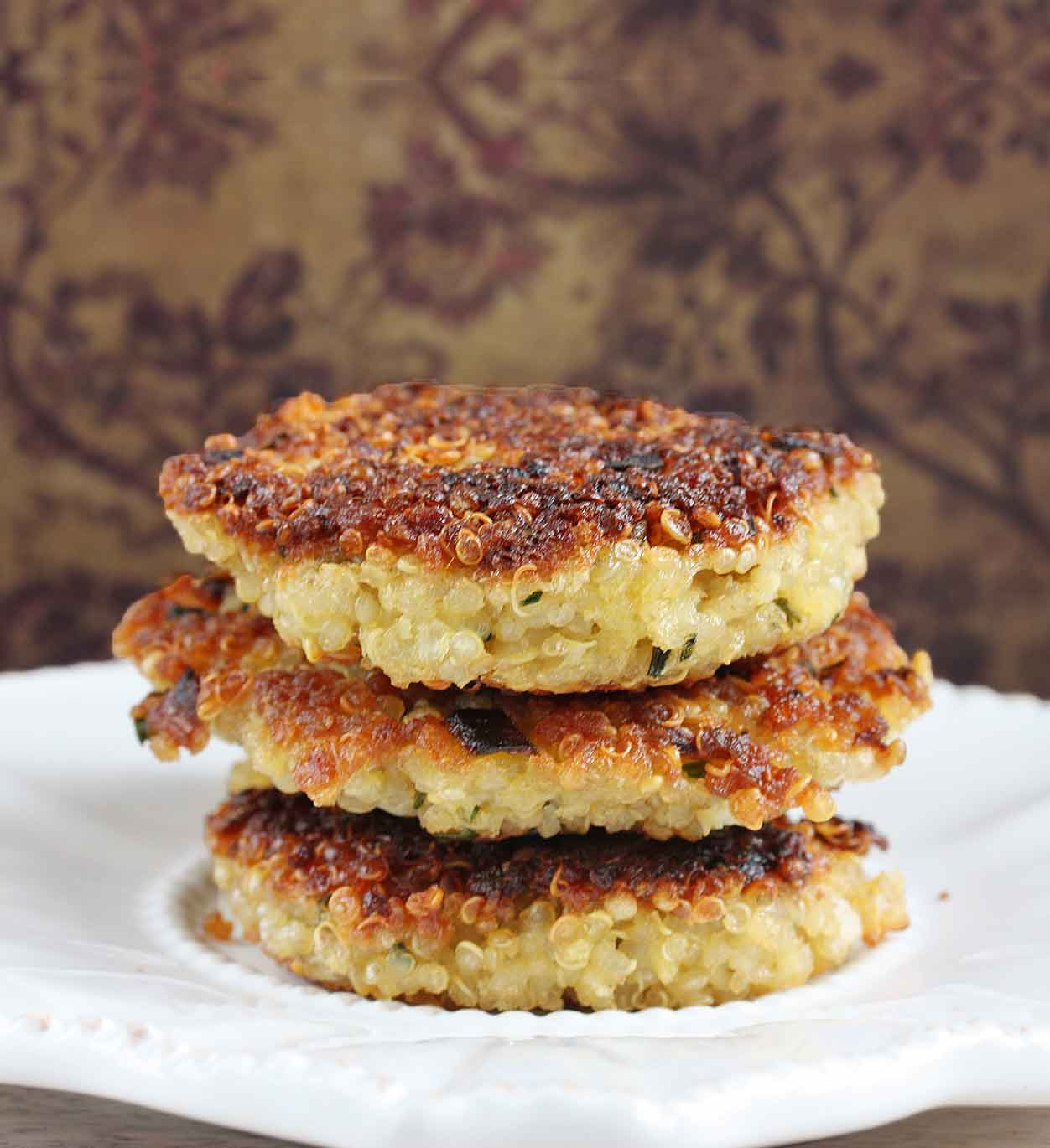 A stack of three quinoa patties on a white plate