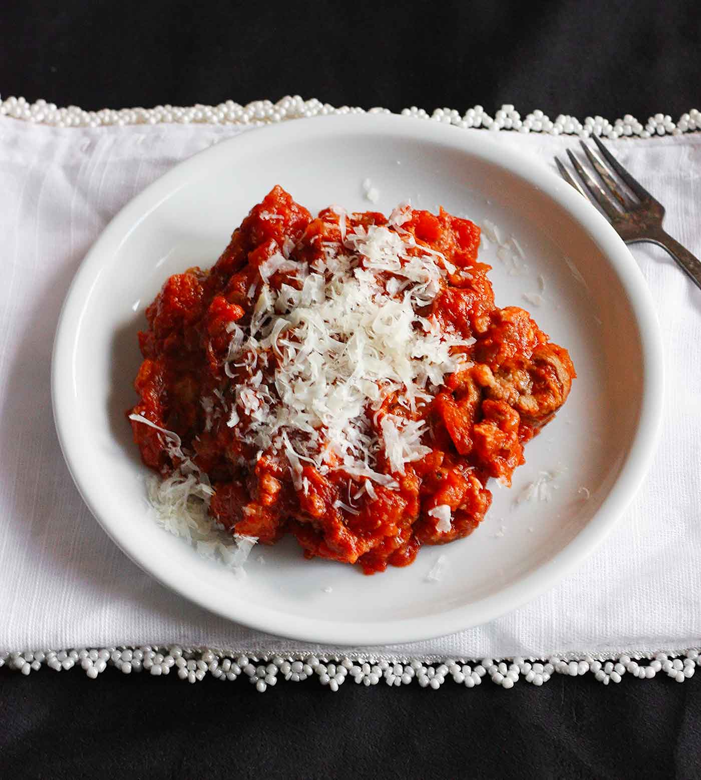 Braciole with sauce and grated cheese on a plate