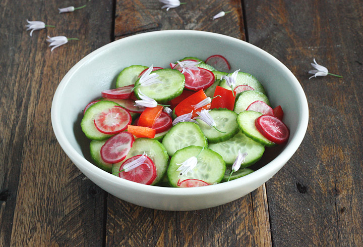 Chive Flower Cucumber Salad in a bowl.