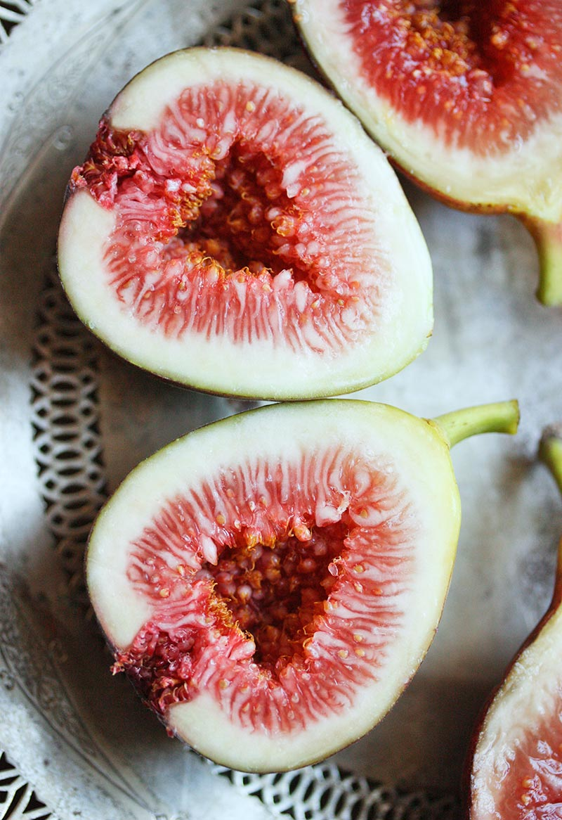 Close-up of fresh figs, sliced in half, in prep for Figs Prosciutto