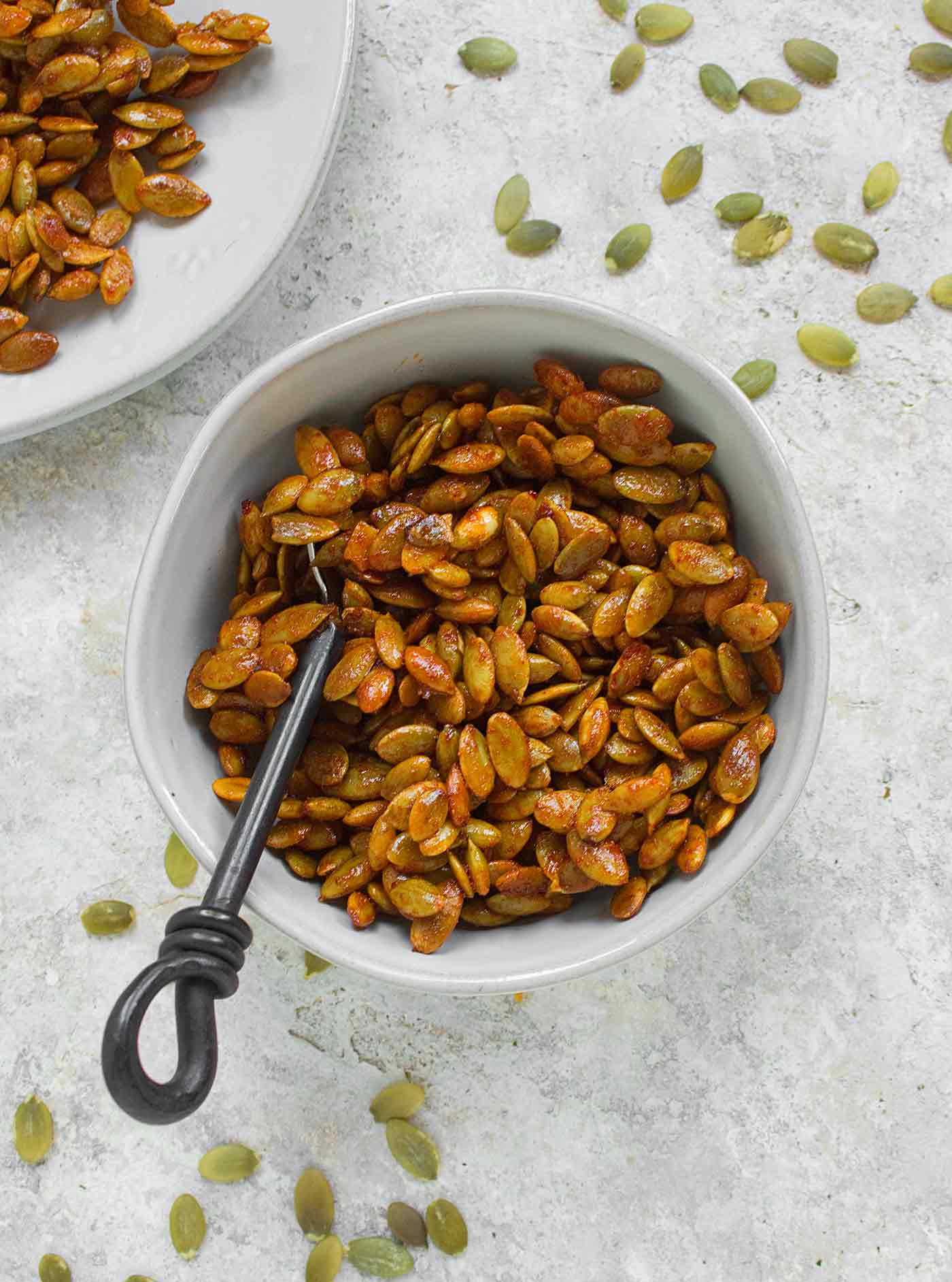 A bowl of honey sriracha pumpkin seeds for snacking