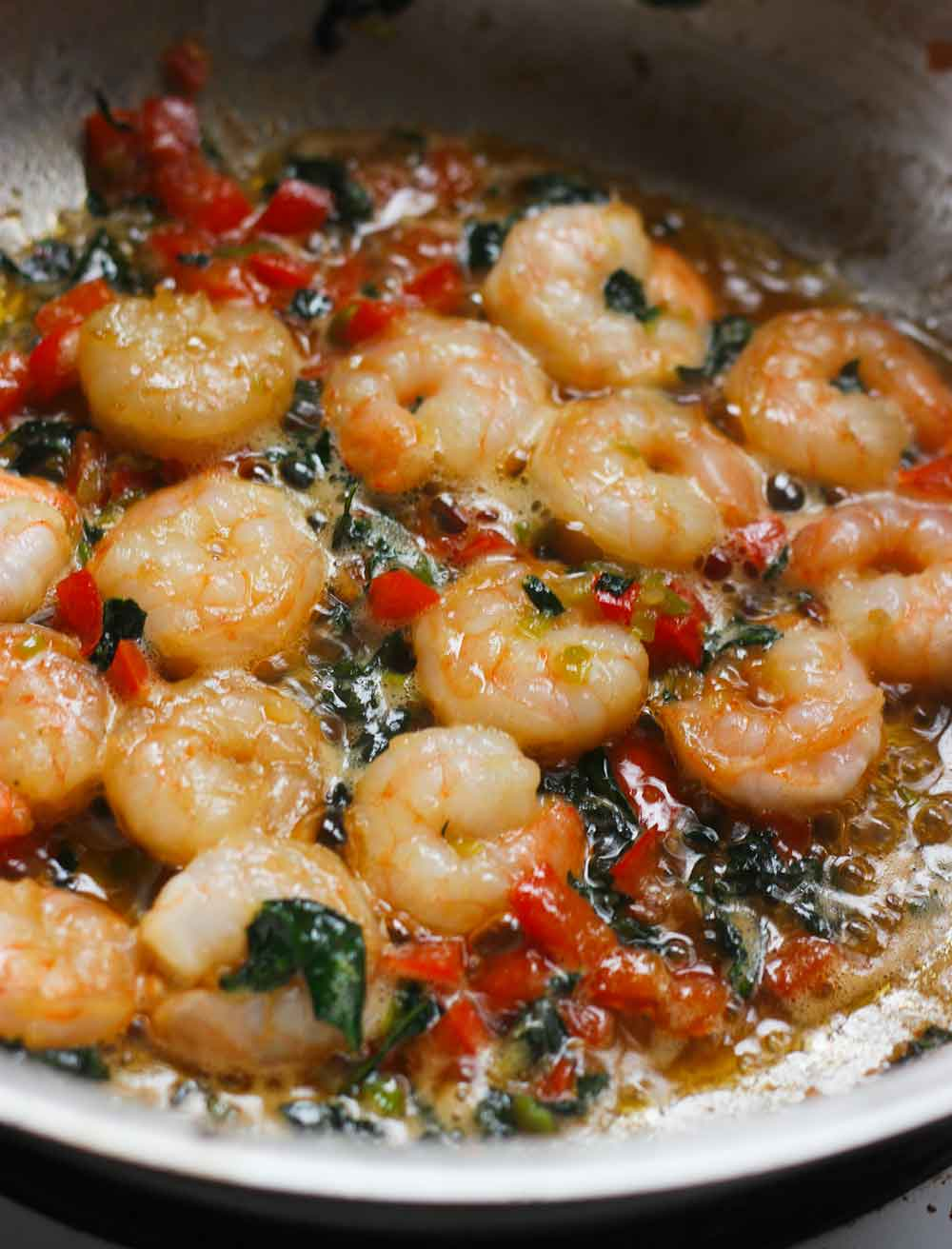 Shrimp and vegetables sauteing in a pan, to be served over spaghetti squash.