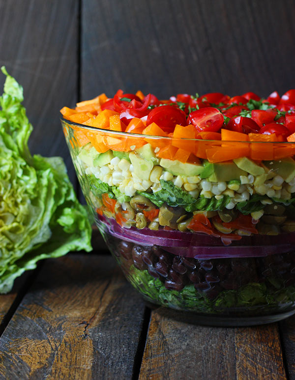 Seven Layer Salad in a large glass bowl, with a head of romain lettuce next to it