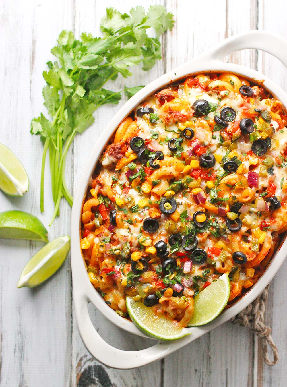 Overhead photo of Mexican Pasta Bake in a white baker with herbs