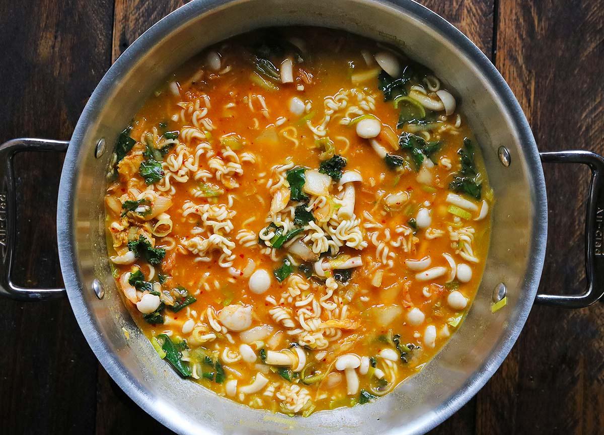 Cooking kimchi ramen noodle soup in a pot