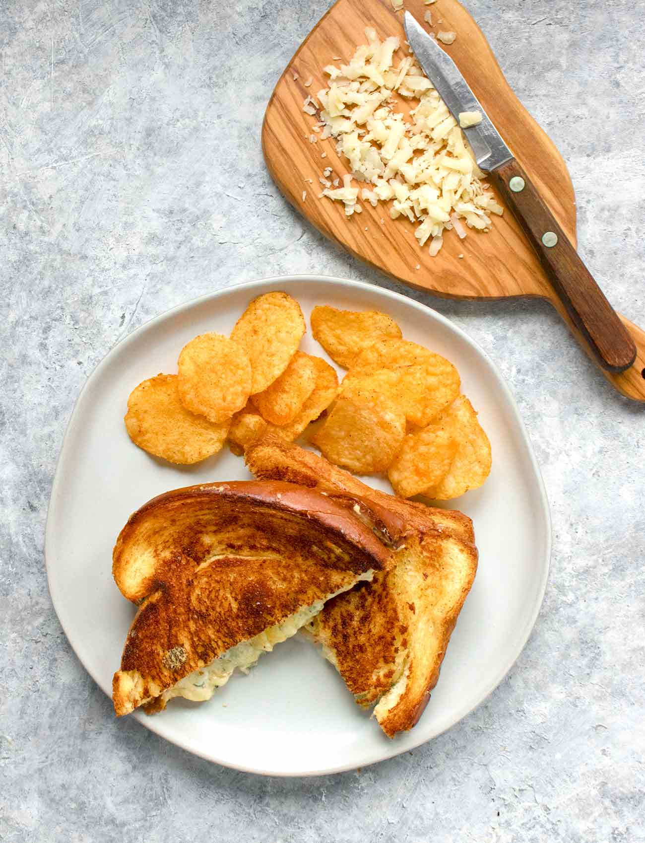 Ultimate grilled cheese sandwich on a plate with potato chips