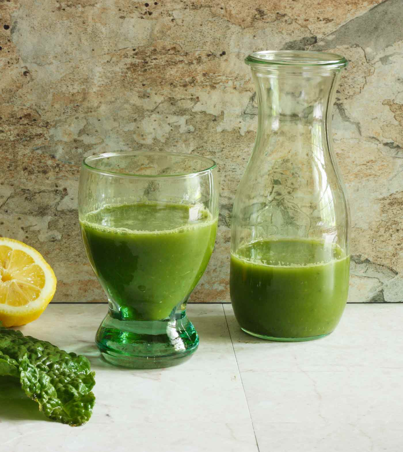 freshly pressed green juice in a glass and a carafe