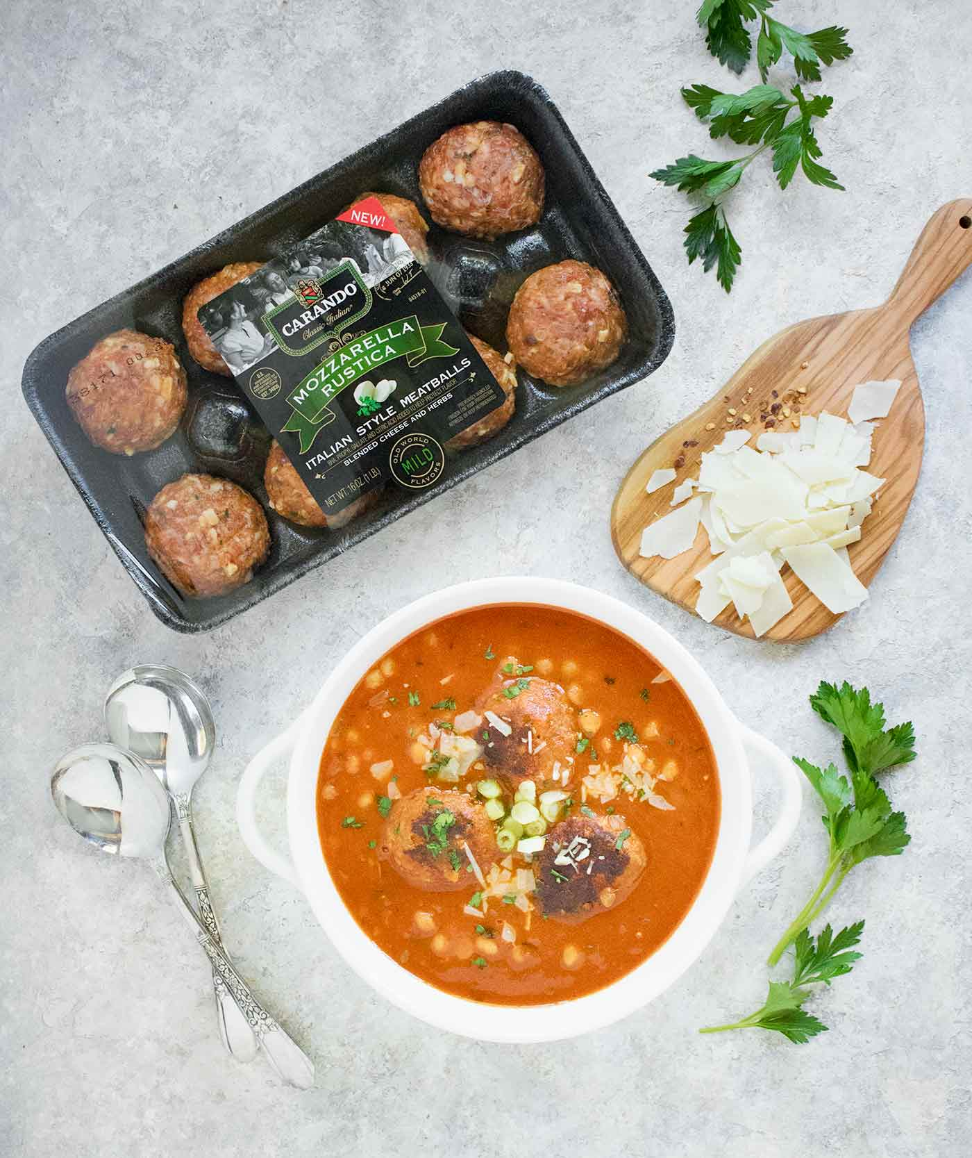 Package of Carando meatballs with the finished Instant Pot Italian Meatball Soup, with a garnish of parm