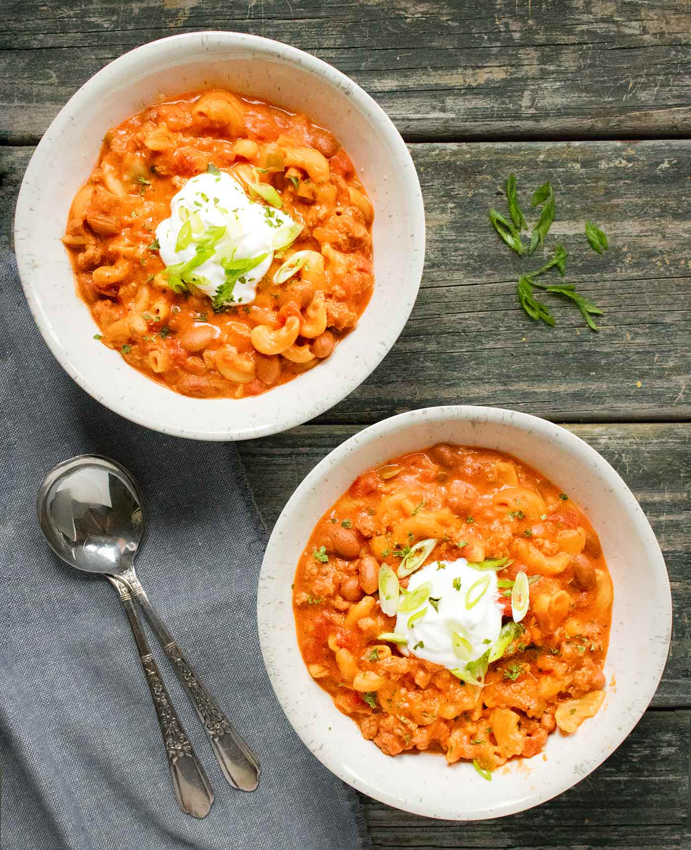 Two bowls of Instant Pot Chili Mac with Turkey, topped with sour cream and green onions