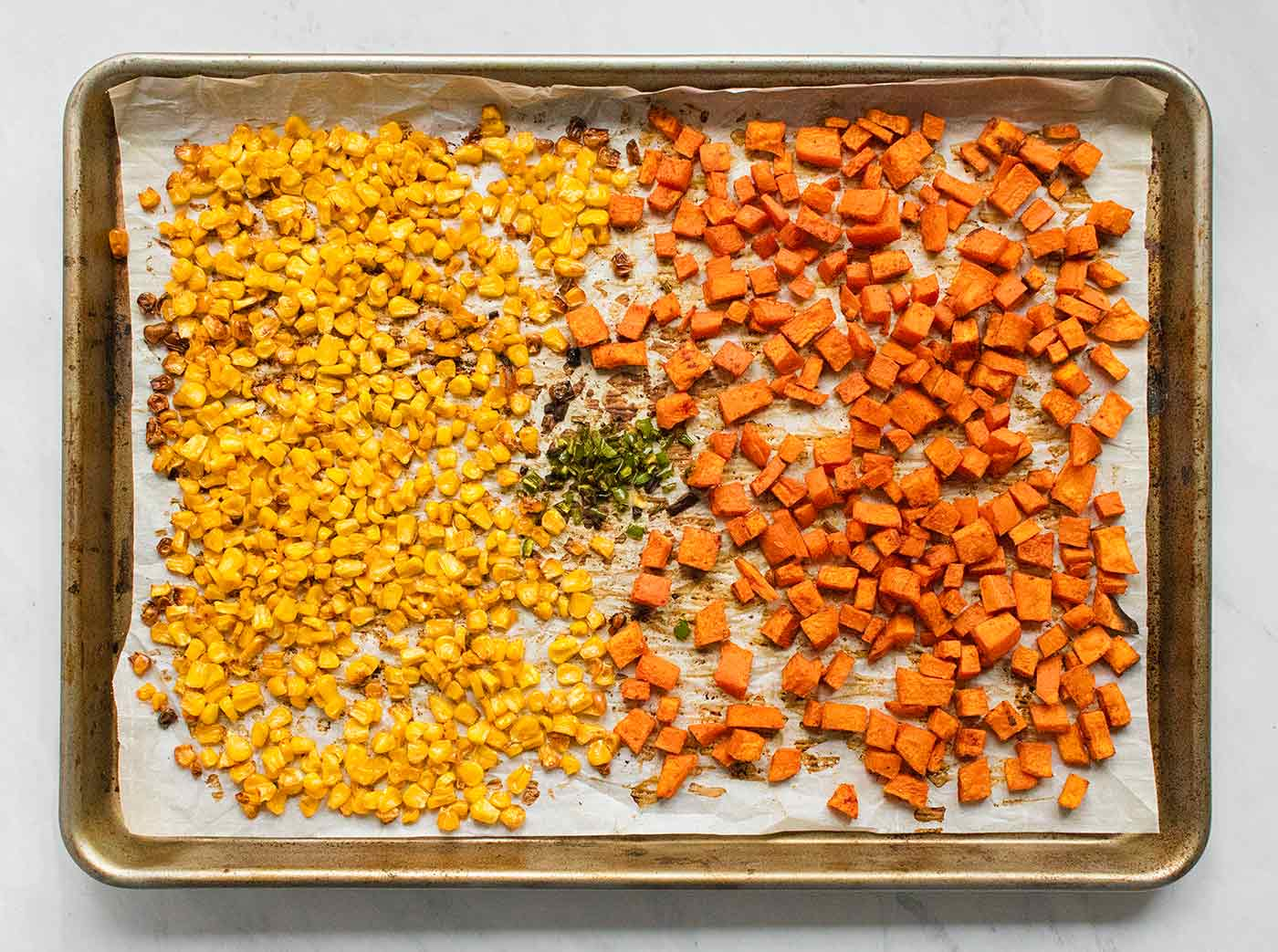 Sheet pan full of roasted vegetables for Sweet Potato Nachos.