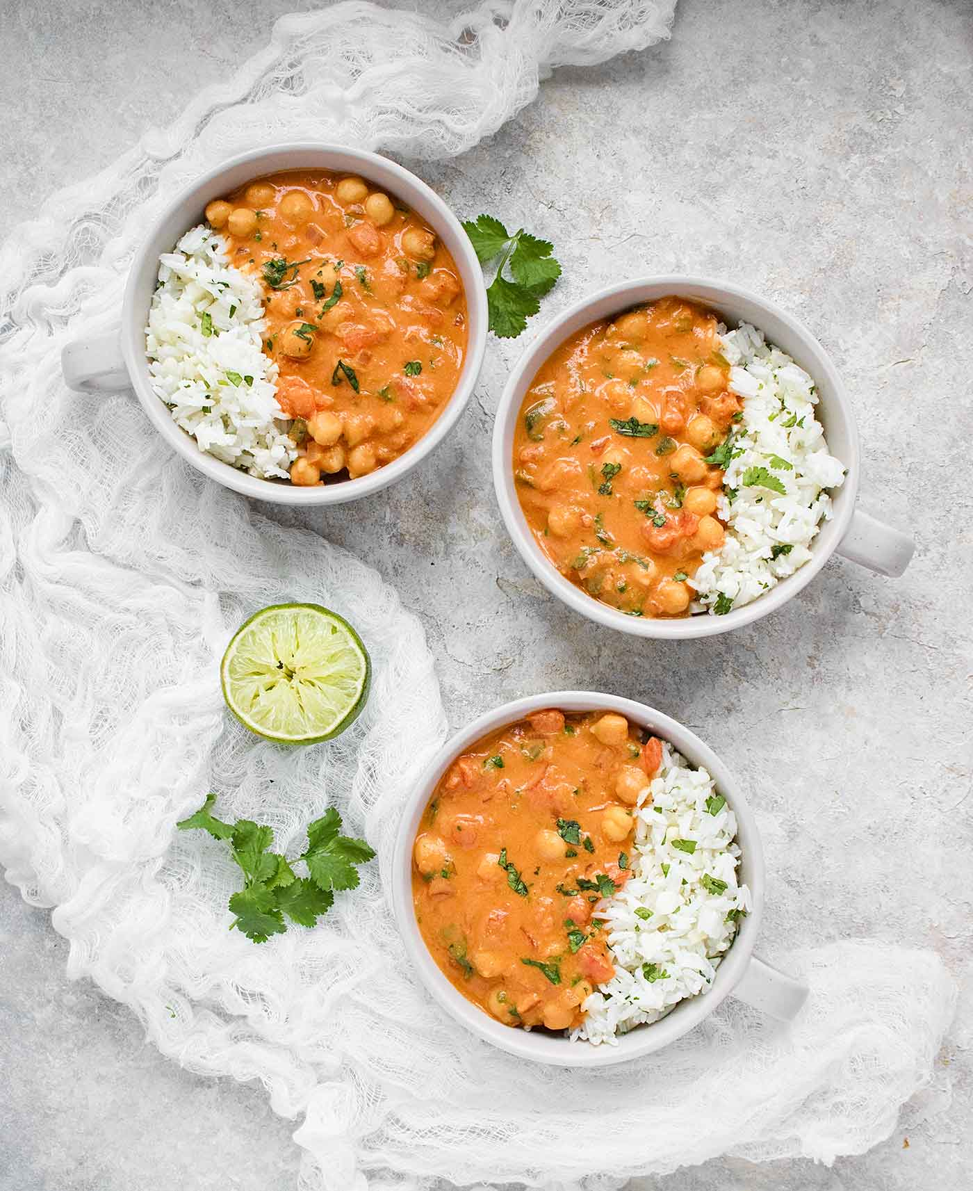 Three bowls of chickpea peanut stew served with cauliflower rice blend