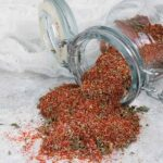 Creole Seasoning spilling out of a glass spice jar