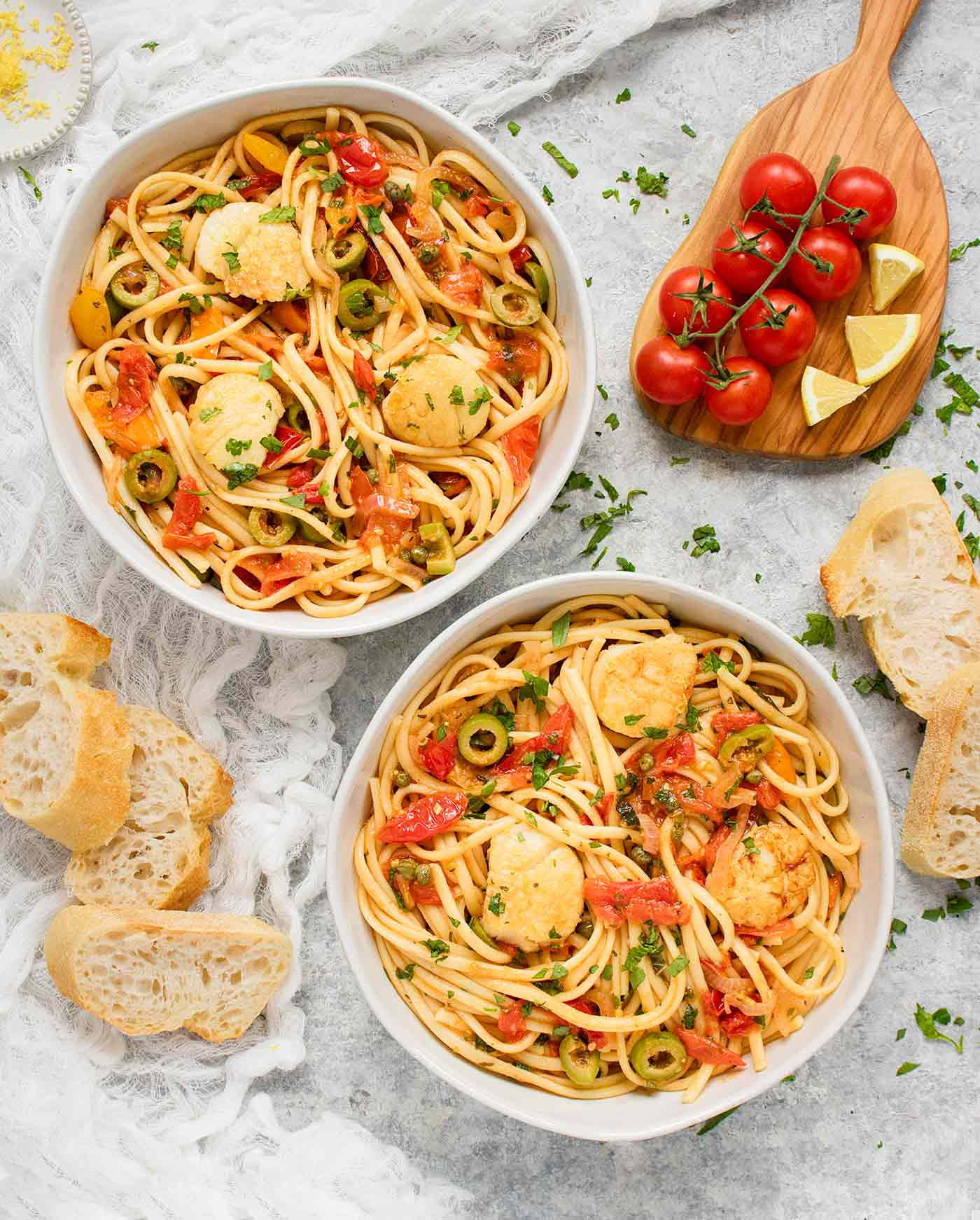 Two bowls of Mediterranean Scallop Linguine with bread on the side