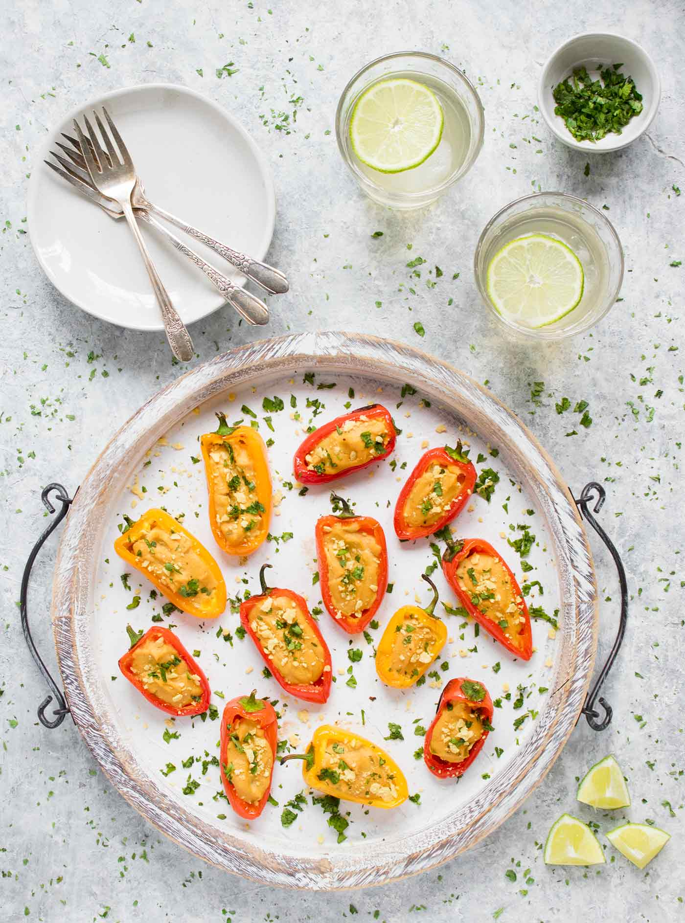Vegan queso stuffed mini peppers on a large white serving tray, with margaritas