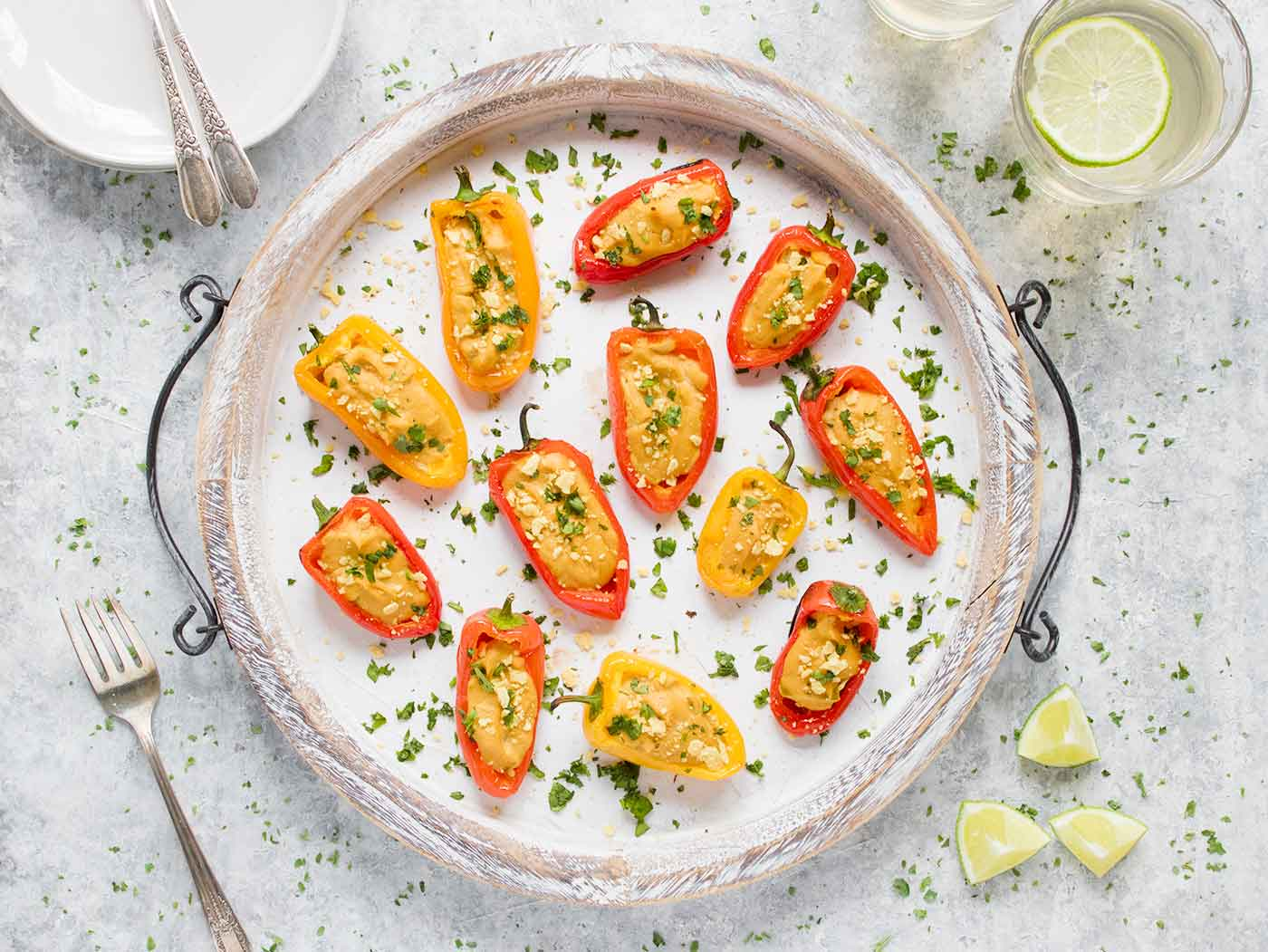Vegan Queso Stuffed Mini Peppers on a large white serving tray