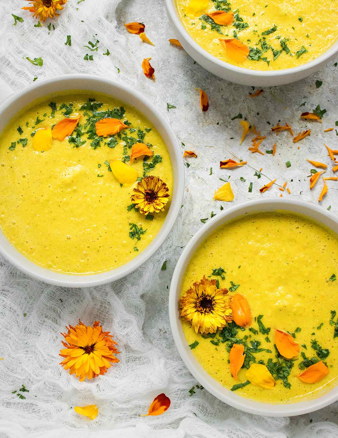 Close-up of three bowls of yellow gazpacho with edible flowers
