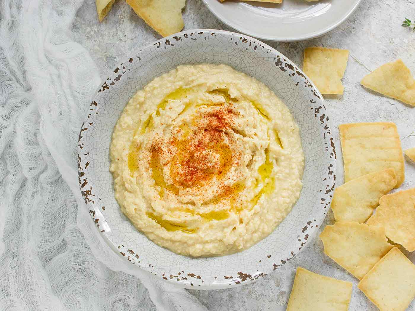 Smoked corn hummus in a bowl with a side of pita chips