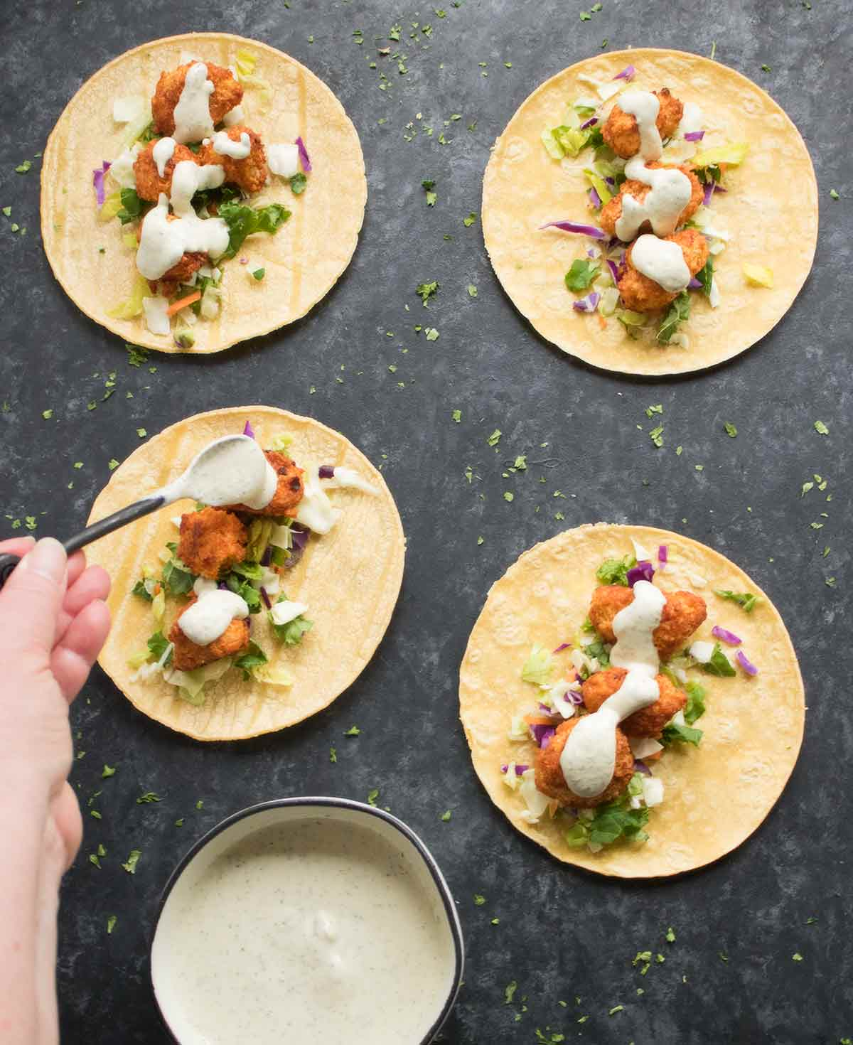 Topping the cauliflower tacos with the vegan ranch dressing
