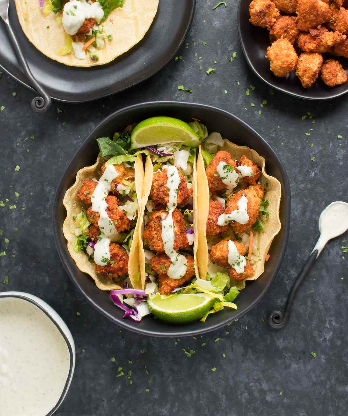 Three sriracha cauliflower tacos topped with vegan ranch dressing in a bowl.