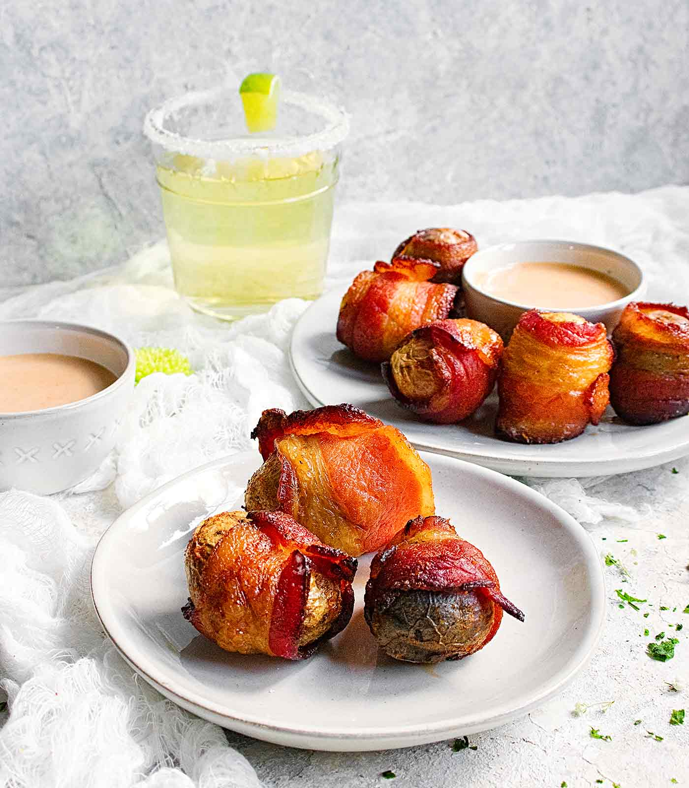 Bacon wrapped potatoes served on individual plates with dipping sauce on the side