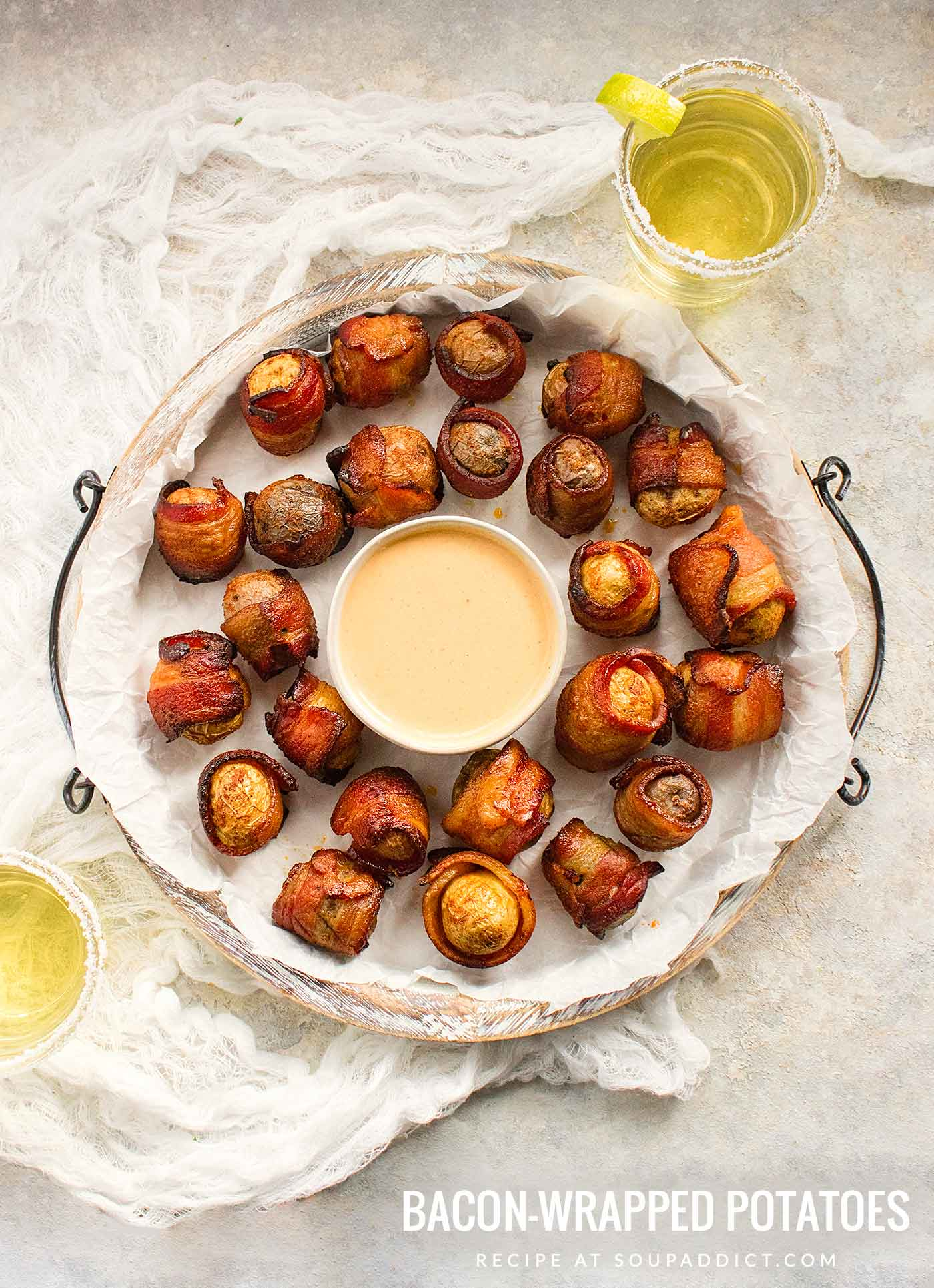 Bacon wrapped potato appetizers on a white serving platter