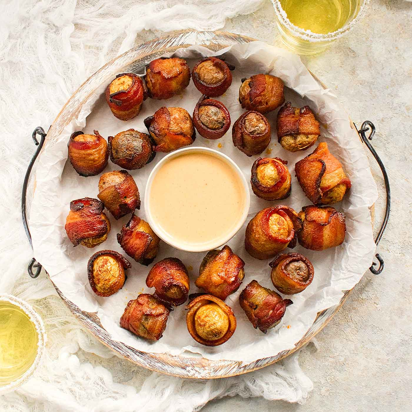 Bacon wrapped baby potatoes with BBQ ranch dipping sauce on a platter