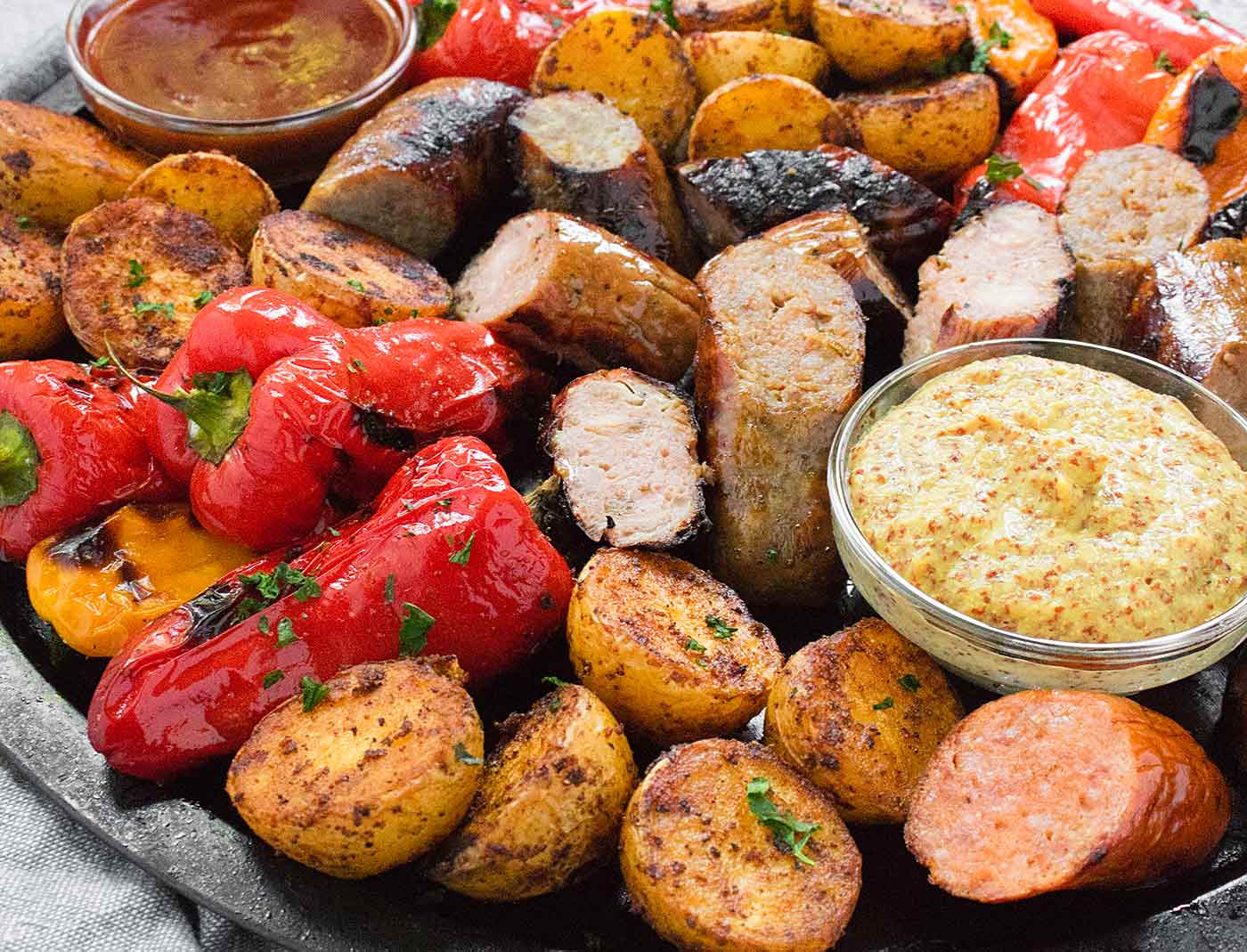 Grilled sausages, peppers, and potatoes on a platter with dipping sauces