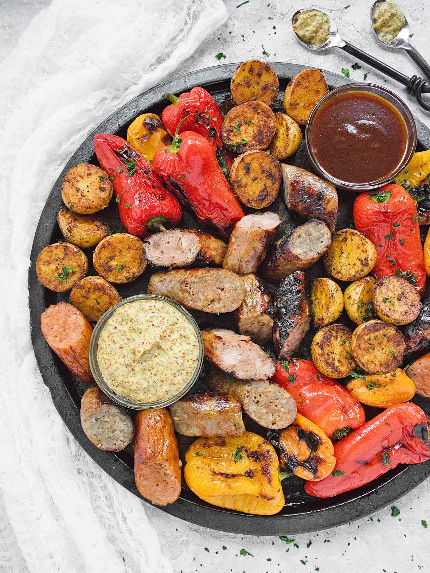 Overhead shot of platter of grilled sausages, peppers, potatoes with dipping sauces