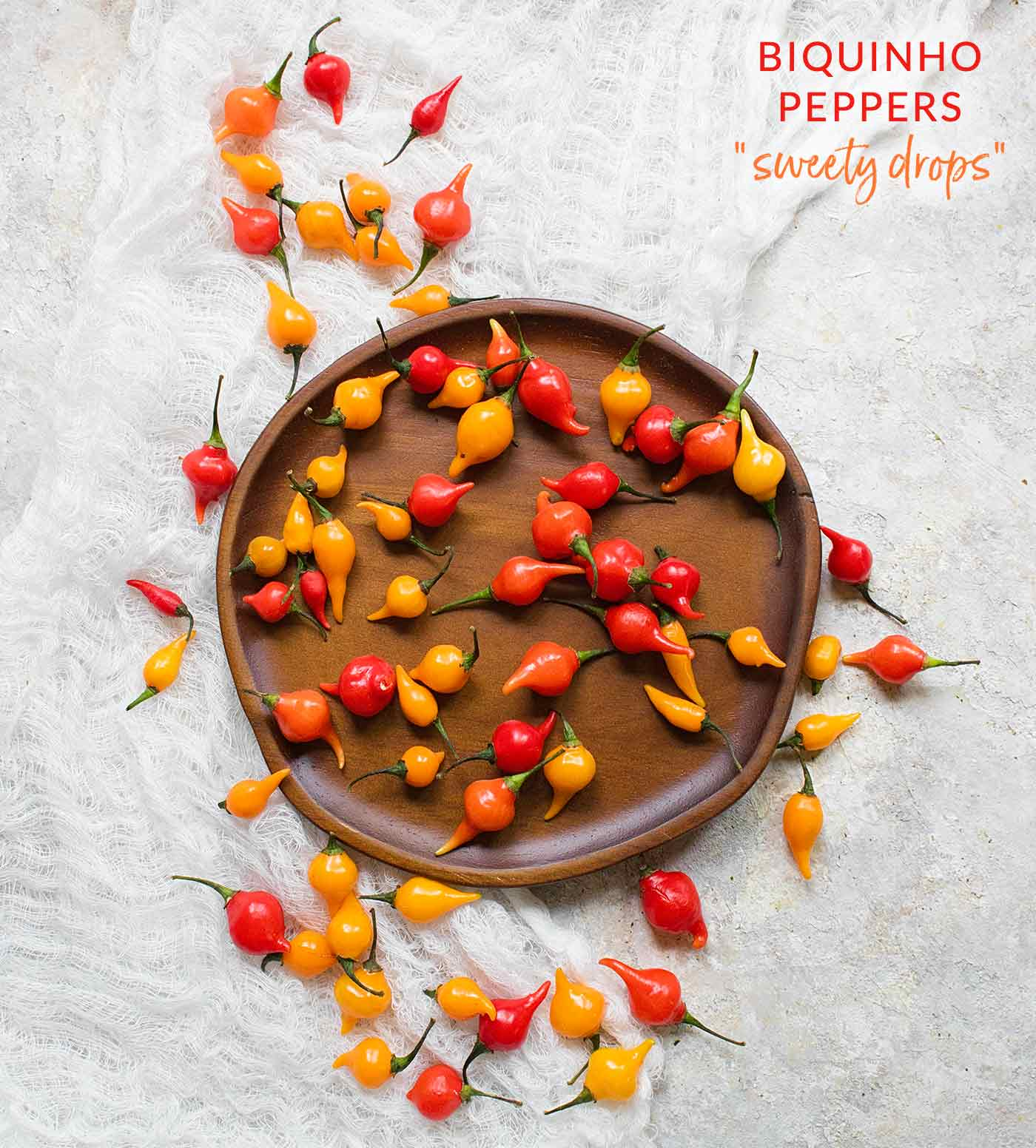 A scattering of red and yellow Biquinho peppers (Peruvian Sweety Drops) on a wooden plate.