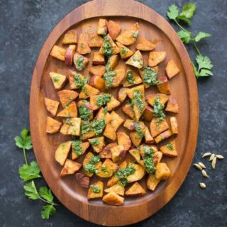 Spiced Sweet Potatoes with cilantro sauce on a wooden serving platter
