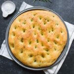A round of freshly baked rosemary focaccia on a pizza pan