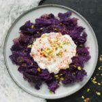 A plate of Instant Pot Okinawan Sweet Potatoes topped with coconut milk and feta cream