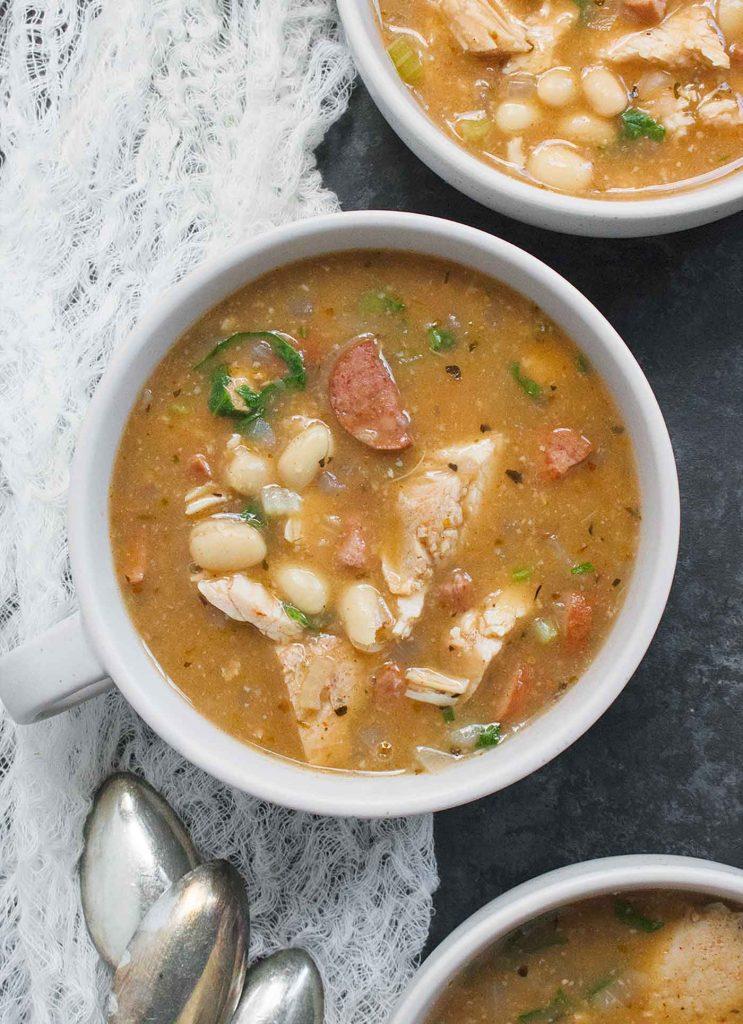 A light grey bowl of Turkey White Bean Soup.