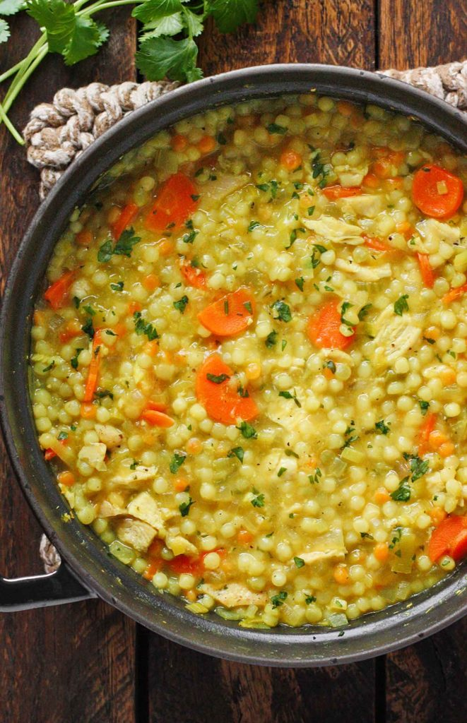 A black Dutch oven with Cold-Fighting Chicken Couscous Soup.