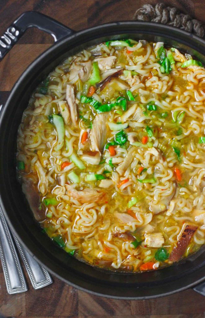 A black Dutch oven filled with Thai Ramen Noodle Chicken Soup
