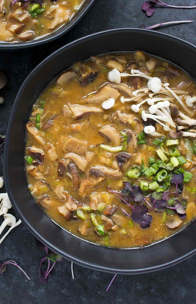 A black bowl of Detox Wild Mushroom Miso Soup.