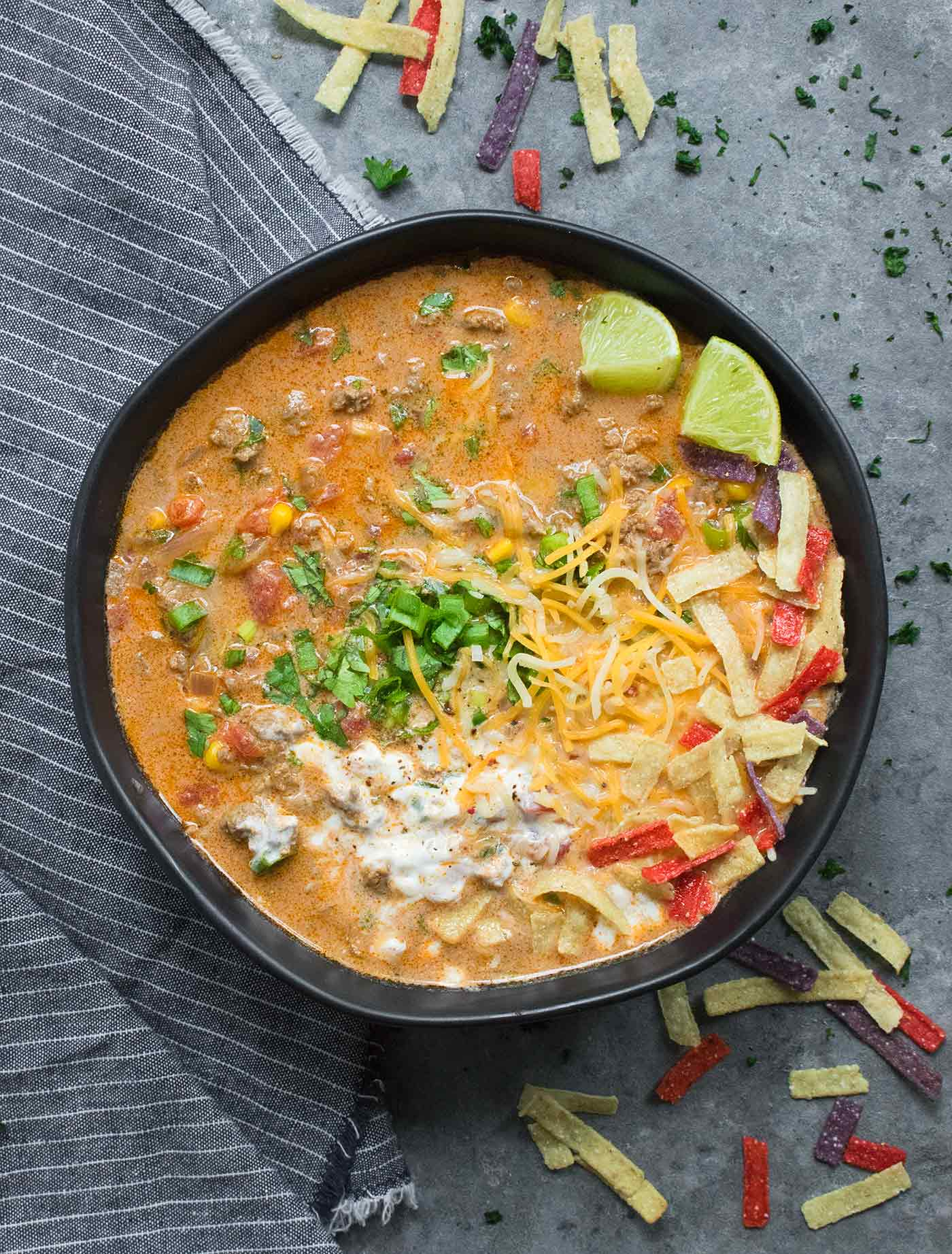 Taco Soup in a large black soup bowl, with toppings.